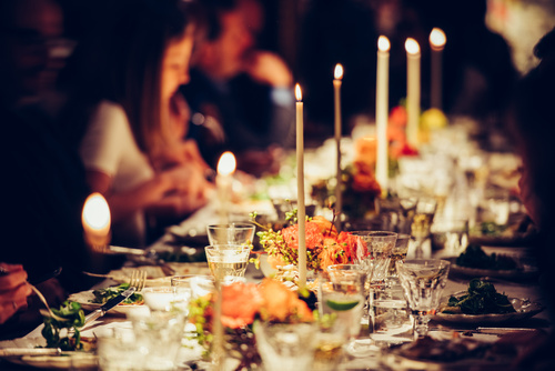 People enjoy a family dinner with candles. Big table served with