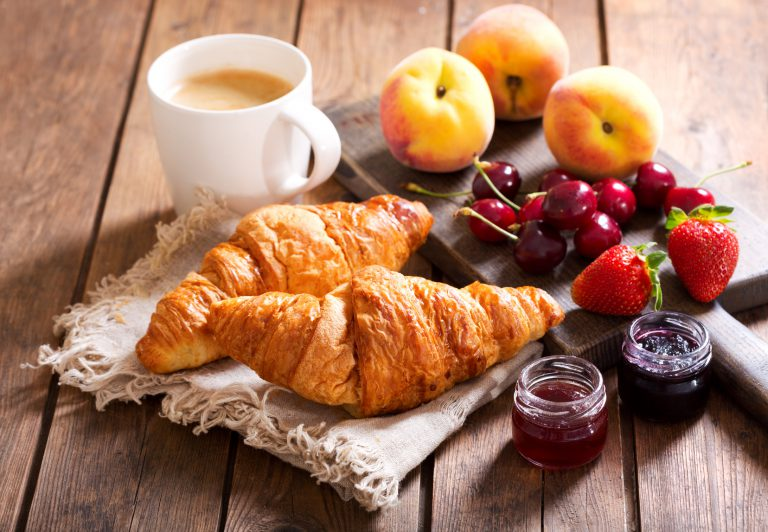 breakfast with croissants, coffee and fresh fruits on wooden table