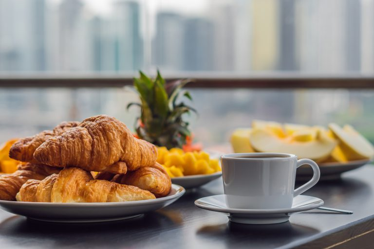 Breakfast table with coffee fruit and bread croisant on a balcony against the backdrop of the big city.